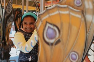 A student riding a butterfly on a carousel.