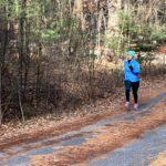 Ale runs along a tree-covered road while training to run the 2020 Boston Marathon© for 826 Boston.