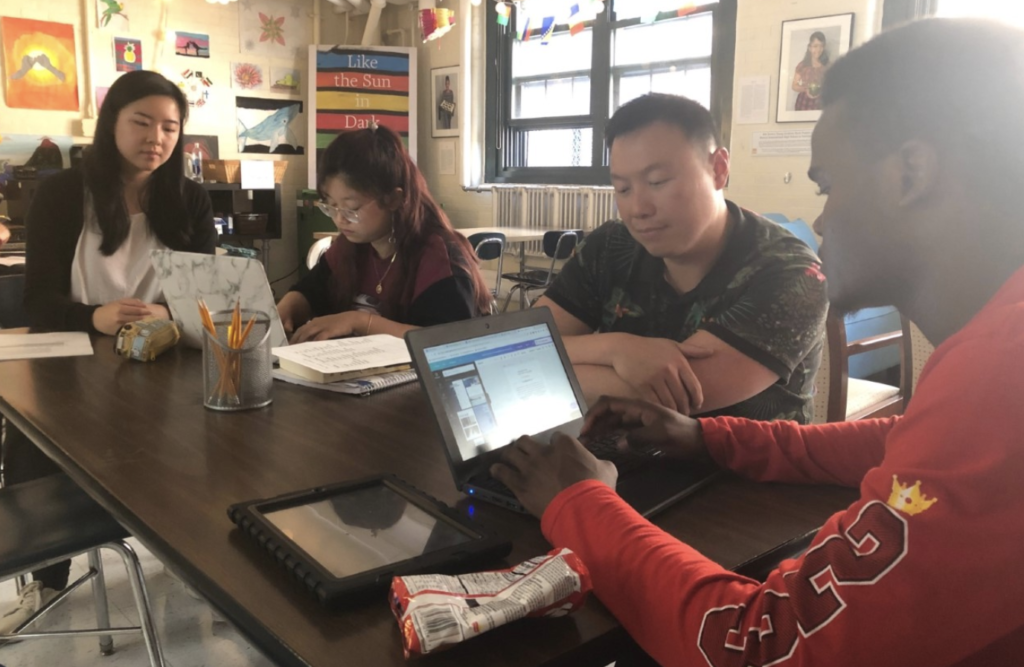 AmeriCorps member Ivan Ang writes with students at Boston International Newcomers Academy.
